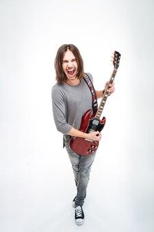 Lustiger junger mann mit langen haaren und offenem mund singt und spielt e-gitarre auf weißem hintergrund