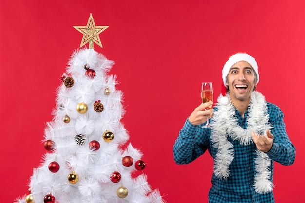 Lustiger junger mann mit weihnachtsmannhut in einem blauen gestreiften hemd, das ein glas wein hält