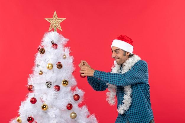 Lustiger junger mann mit weihnachtsmannhut in einem blauen gestreiften hemd und halten