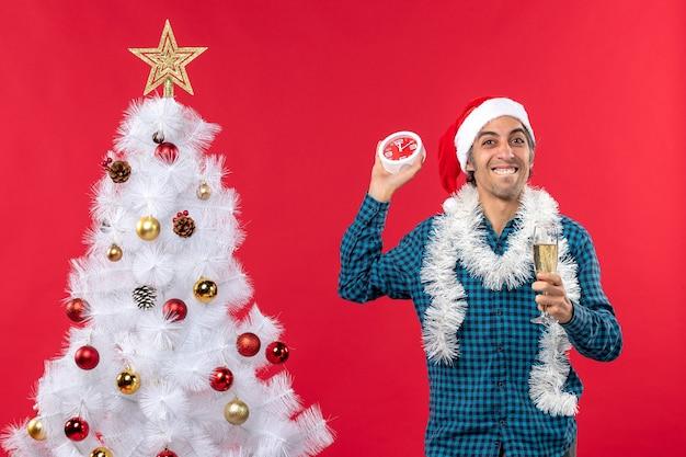 Lustiger junger mann mit weihnachtsmannhut und dem erhöhen eines glases wein und des haltens der uhr, die nahe weihnachtsbaum auf rot steht