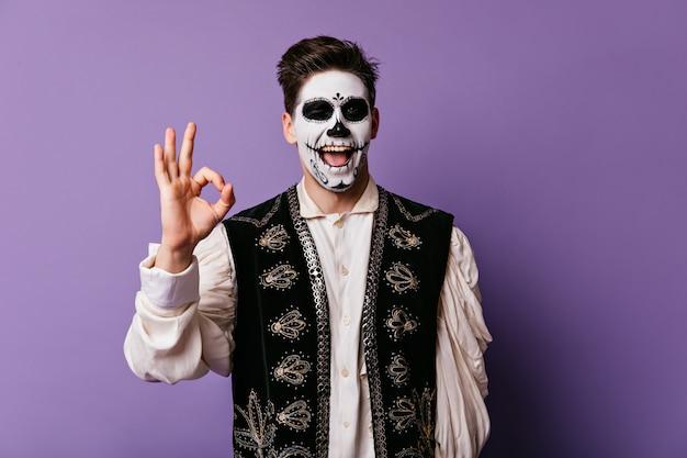 Lustiger junger mann zeigt zeichen ok. innenporträt des kerls mit gesicht gemalt für halloween.