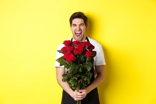 Lustiger junger verkäufer in schwarzer schürze mit rosenstrauß, florist lachend und stehend über gelbem hintergrund.