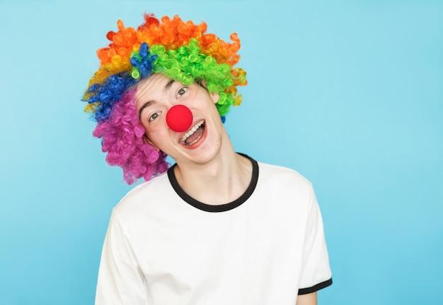 Lustiger kerl in einem clownkostüm auf einem blau