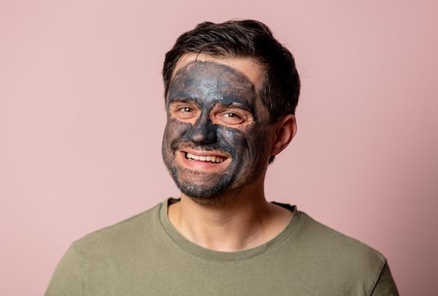 Lustiger kerl mit einer kosmetischen maske auf seinem gesicht auf rosa