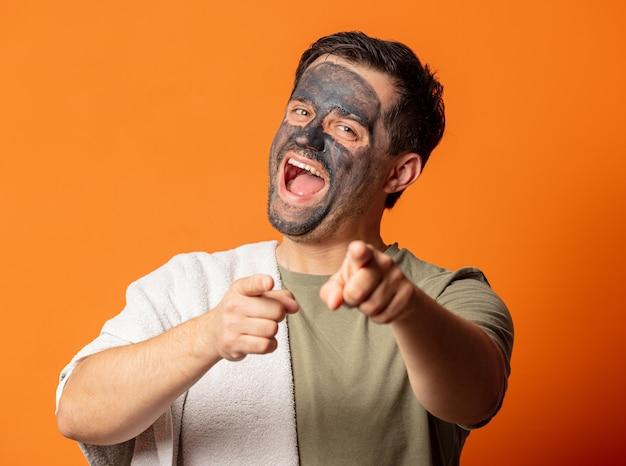 Lustiger kerl mit einer kosmetischen maske auf seinem gesicht und handtuch auf orange