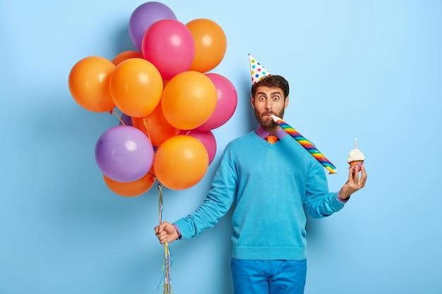 Lustiger kerl mit geburtstagshut und luftballons, die im blauen pullover aufwerfen