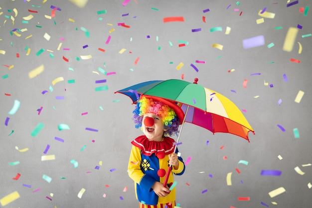 Lustiger kinderclown gegen fallendes konfetti.
