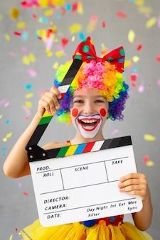 Lustiger kinderclown. glückliches kind, das zu hause spielt. 1. april narrentagskonzept