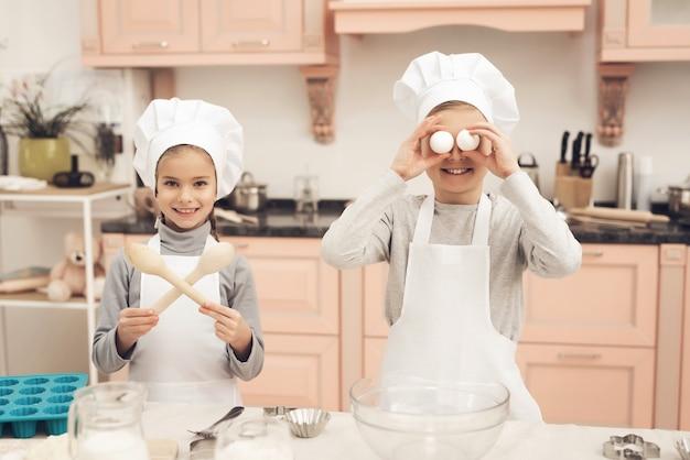 Lustiger kinderjunge und -mädchen-spiel an der küche zu hause.