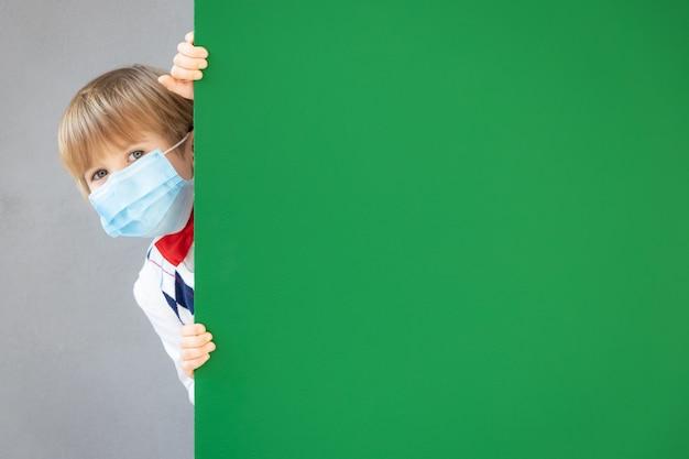 Lustiger kinderschüler, der schutzmaske in der klasse trägt. glückliches kind, das sich hinter grüner tafel versteckt.
