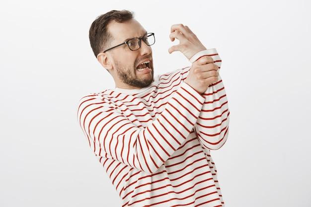 Lustiger kindischer erwachsener mann mit borste in der brille, der versucht, angriff der hand zu halten, arm zu halten und vor angst zu schreien
