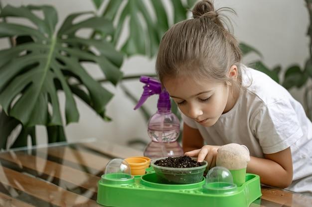Lustiger kleiner gärtner mit pflanzen im zimmer zu hause, der zimmerpflanzen wässert und pflegt, blumen verpflanzt.