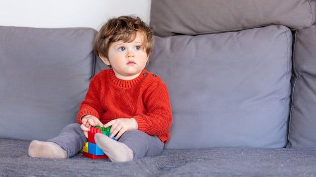 Lustiger kleiner junge, der auf sofa in der roten strickjacke sitzt