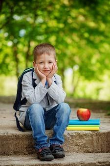 Lustiger kleiner junge, der auf stein mit büchern, apfel und rucksack auf grünem naturhintergrund sitzt. zurück zum schulkonzept.