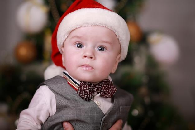 Lustiger kleiner junge, der in der weihnachtsmannmütze mit auf weihnachtsbaumwand getragen wird.