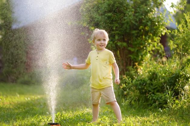 Lustiger kleiner junge, der mit gartenberieselungsanlage im sonnigen hinterhof spielt