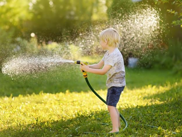 Lustiger kleiner junge, der mit gartenschlauch im sonnigen hinterhof spielt. vorschulkind, das spaß mit spray des wassers hat.