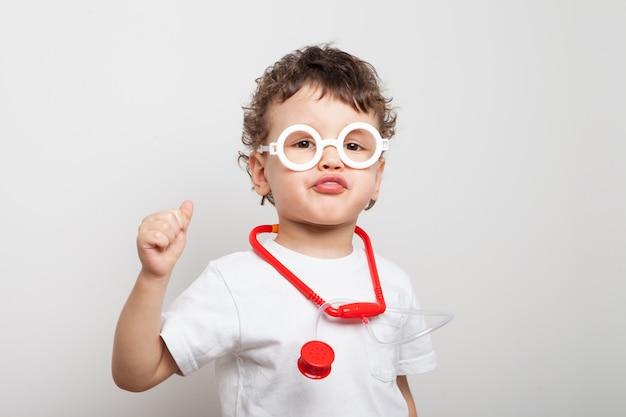 Lustiger kleiner junge in der brille, ein kleinkind im arztanzug, in der weißen brille und mit einem stethoskop. ein begeisterter blick. medizinische verfahren. spiel im beruf. isolierter weißer hintergrund