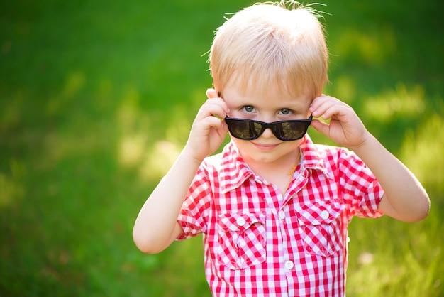 Lustiger kleiner junge in der sonnenbrille. kinderjunge in der sonnenbrille, die in der kamera am sommertaghintergrund schaut