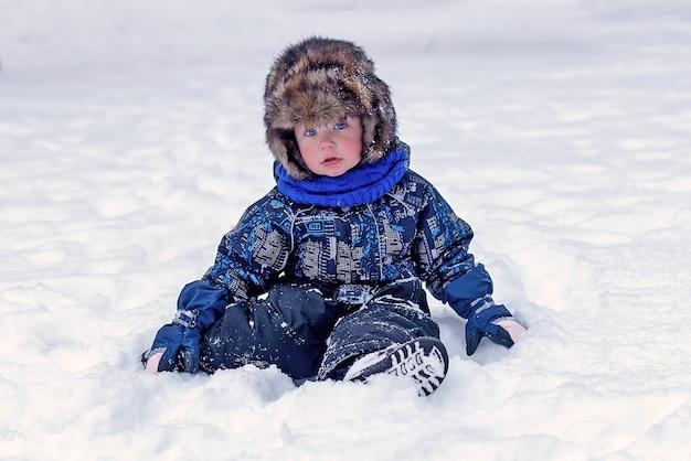 Lustiger kleiner junge in overalls und pelzmütze kleidung, die draußen während des schneefalls spielt. aktive erholung mit kindern im winter an kalten schneetagen. glückliches kind.