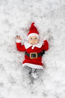 Lustiger kleiner junge in sankt-kostüm ist bereit, weihnachten und neues jahr zu feiern. weihnachtskarte