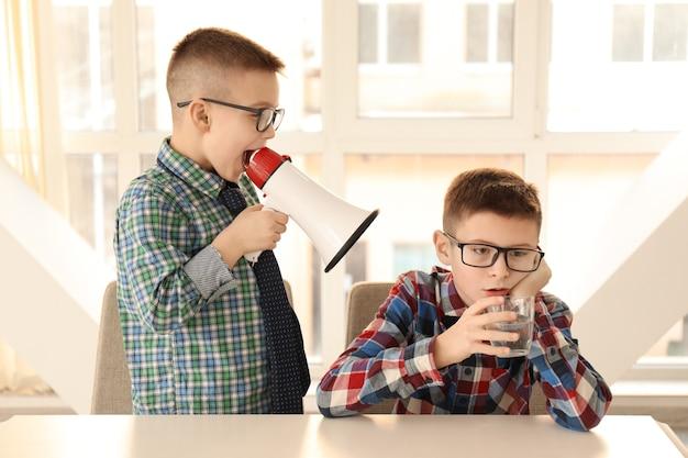 Lustiger kleiner junge mit megaphon, der seinen gelangweilten freund am tisch schreit