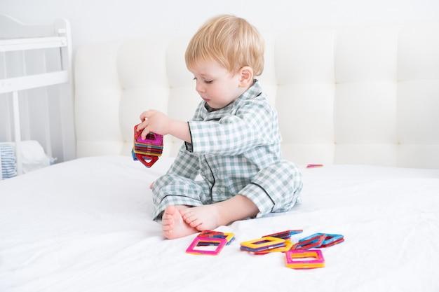 Lustiger kleinkindjunge, der im magnetischen konstruktor auf weißem bett im pyjama spielt