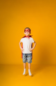 Lustiger kleinkindjunge in einem heldenkostüm ist ungezogen auf einer gelben oberfläche mit einem platz für text