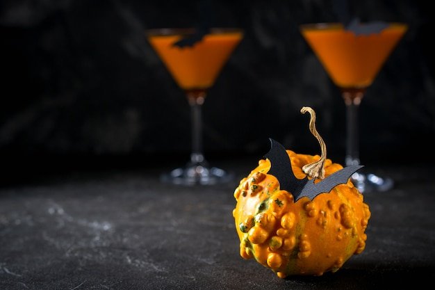 Lustiger kürbis mit schwarzen fledermäusen und orange cocktail in einem glas an halloween