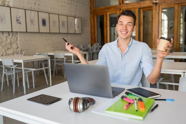 Lustiger lächelnder glücklicher junger mann, der im mitarbeitenden büroraum sitzt und am laptop arbeitet