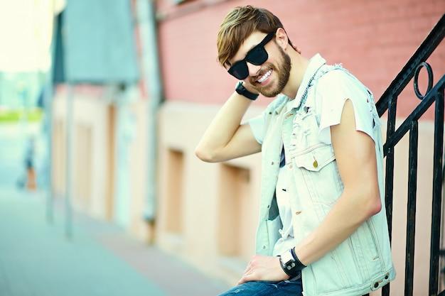 Lustiger lächelnder hipster hübscher mann kerl in stilvollem sommertuch in der straße in der sonnenbrille