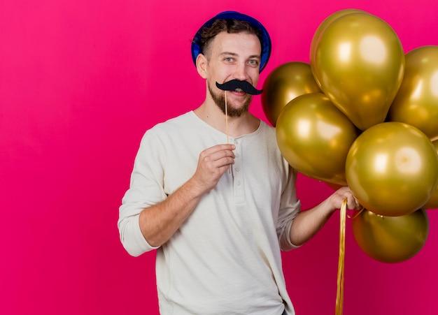 Lustiger lächelnder junger hübscher slawischer party-typ, der partyhut hält, der luftballons und falschen schnurrbart auf stock über lippen hält, die front lokalisiert auf rosa wand mit kopienraum betrachten