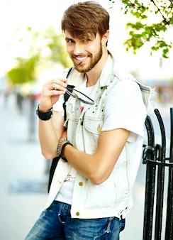 Lustiger lächelnder kerl des gutaussehenden mannes des hippies im stilvollen sommerstoff in der straße in der sonnenbrille