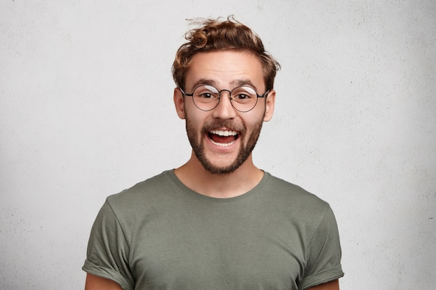 Lustiger lächelnder unrasierter männlicher wonk trägt runde brillen und freizeitkleidung und ist froh