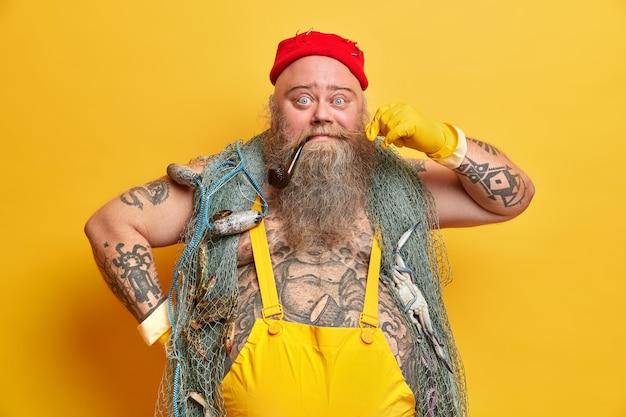 Lustiger männlicher seemann lockt schnurrbart hat pfeife im mund trägt roten hutoverall und handschuhposen