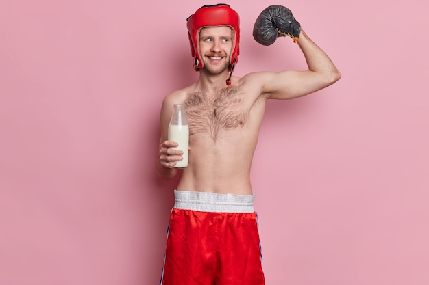 Lustiger männlicher skinny boxer hebt den arm und zeigt, dass muskeln mit nackten torso-drinks milch großartige sportergebnis-posen erzielen wollen