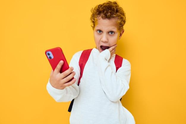 Lustiger männlicher teenager benutzt den gelben hintergrund des telefonbildungskinderlebensstils