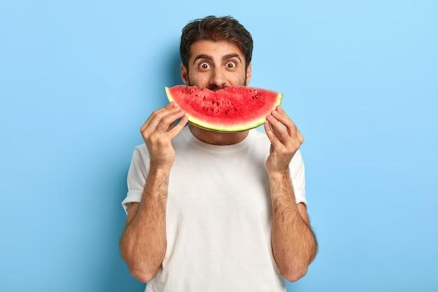 Lustiger mann an einem sommertag, der eine scheibe wassermelone hält