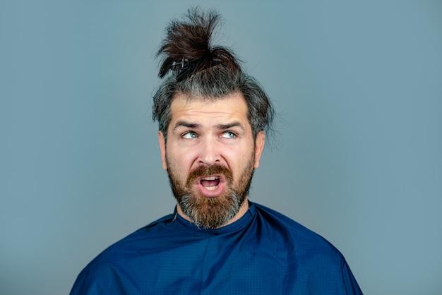 Lustiger mann beim friseur, der einen haarschnitt erhält. hipster-kunde im friseursalon. professioneller friseur, der die haare seines kunden stylt.