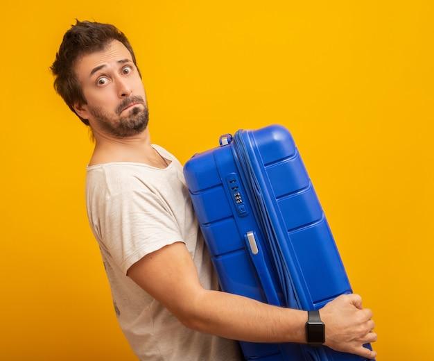 Lustiger mann, der eine schwere reisetasche auf gelb hält