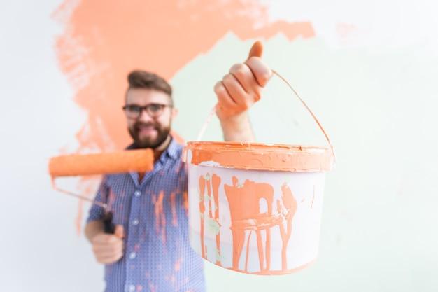 Lustiger mann, der innenwand des hauses malt. renovierungs-, reparatur- und renovierungskonzept.