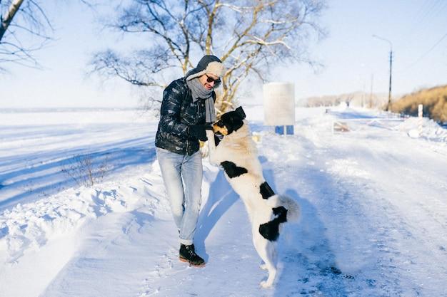 Lustiger mann, der mit hund im kalten wintertag an der natur tanzt.