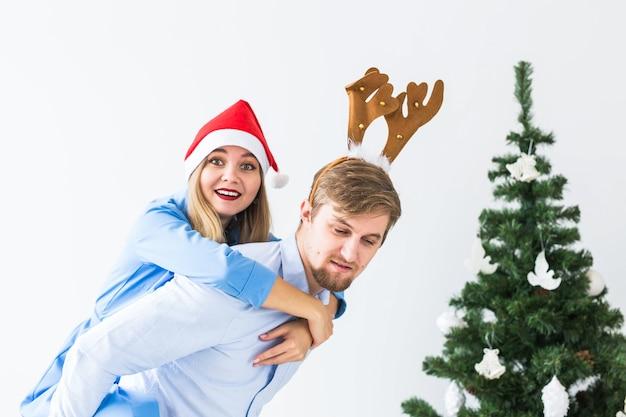 Lustiger mann, der seiner frau huckepack gibt, während sie zu hause weihnachtsmützen für die weihnachtsfeiertage tragen.