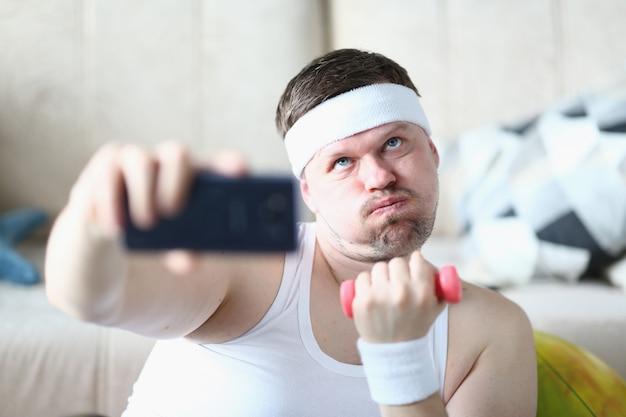 Lustiger mann, der selfie während des morgendlichen trainings zu hause macht
