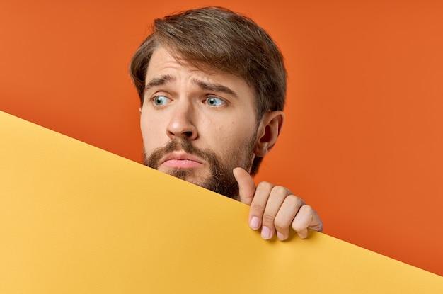 Lustiger mann gelb mockup poster rabatt orange hintergrund. foto in hoher qualität