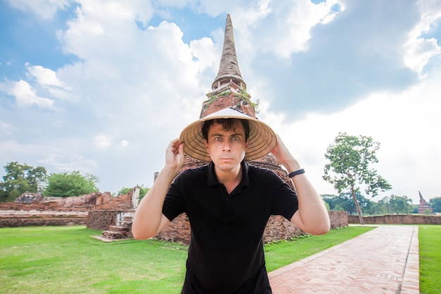 Lustiger mann im chinesischen hut bei wat mahathat in ayutthaya