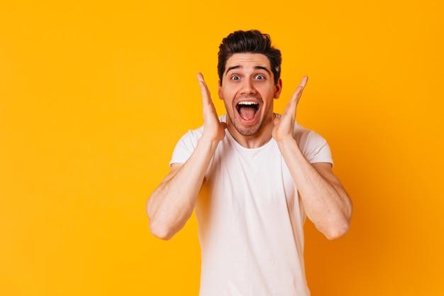 Lustiger mann im weißen outfit schreit freudig und schaut begeistert in die kamera auf orangefarbenem raum.