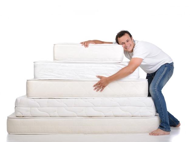 Lustiger mann in den pyjamas, die auf vielen matratzen sitzen.