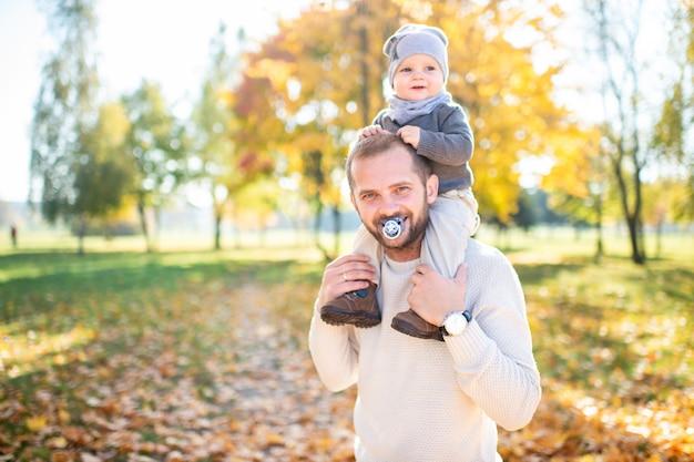 Lustiger mann mit baby-brustwarze in seiner maus und kind auf seinen schultern.