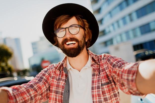Lustiger mann mit bart, der selbstporträt durch kamera macht, während er in der großen modernen stadt in asien reist.